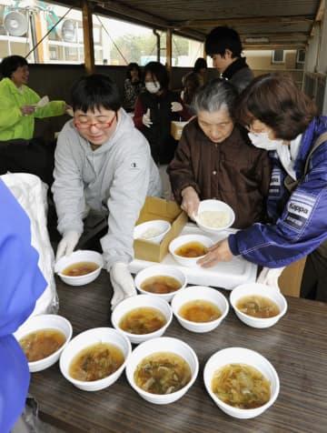 避難所で野菜スープを配膳する人たち=2011年3月20日、宮城県気仙沼市