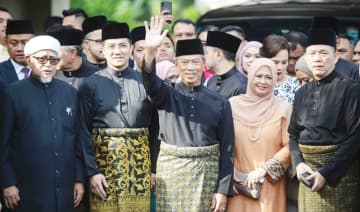 Muhyiddin Yassin waves outside his residence in Kuala Lumpur on Sunday before his swearing-in ceremony as Malaysia's new leader.