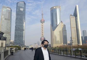 2月、中国・上海市中心部でマスクを着けて出勤する男性(共同)