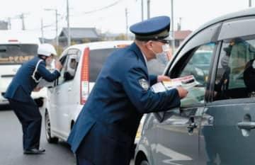 情報提供を求めてチラシを配布する大分東署員ら=2日午前、大分市松岡の松岡郵便局前