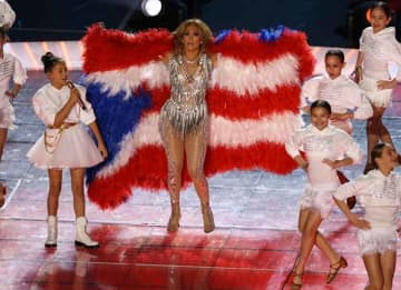 MIAMI, FLORIDA - FEBRUARY 02: Singer Jennifer Lopez and her daughter Emme Maribel Muñiz perform while a Puerto Rican flag is displayed on stage during the Pepsi Super Bowl LIV Halftime Show at Hard Rock Stadium on February 02, 2020 in Miami,...