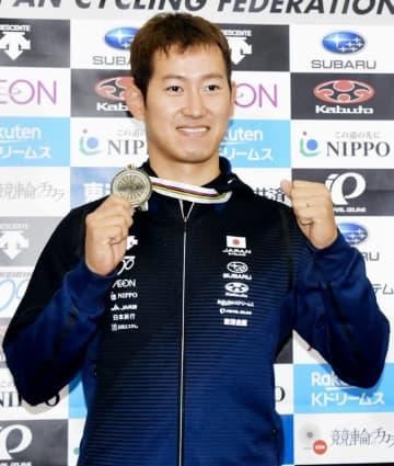 自転車トラック種目世界選手権男子ケイリンの銀メダルを掲げガッツポーズの脇本雄太=3月3日、成田空港