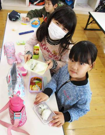 無償提供されたおにぎりを手にして喜ぶ児童たち=吉野ヶ里町の三田川放課後クラブ(同町提供)