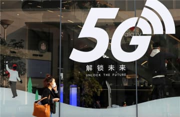 A pedestrian walks past a sign promoting 5G services outside a mobile phone shop in Shanghai. [Photo by Chen Yuyu/For China Daily]