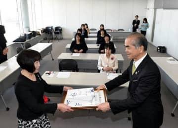 松田理事長(右)から表彰状などを受け取る優良保育士