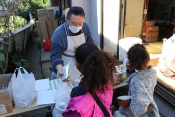 弁当を受け取る児童ら=横須賀市池上4丁目の「よこすかなかながや」