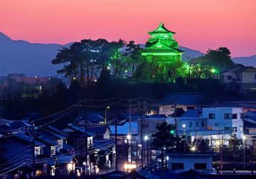 世界緑内障週間のスタートに合わせ、緑色にライトアップされた丸岡城天守=3月8日午後6時25分ごろ、福井県坂井市丸岡町八ケ郷から撮影