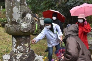 高僧「衛徳坊」の石像などを見学した「春の史跡巡り」の参加者