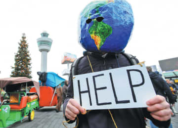 A protester makes a point at a Greenpeace climate demonstration at Amsterdam Airport Schiphol in the Netherlands on Jan 4, 2020. [Photo/Agenceis]