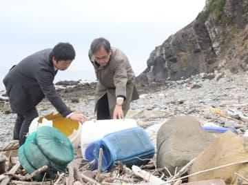 対馬の環境団体関係者と、打ち上げられた漂着ごみを確認する長崎大の山本副学長(右)=対馬市厳原町上槻