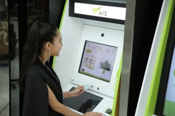A young woman processes mobile phone bills at an AIS shop using facial recognition. The Bank of Thailand is exploring ways to use mobile phone bills for credit scoring.