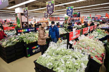 Residents shop in a Wumart store for vegetables and other daily necessities. [Photo provided to chinadaily.com.cn]