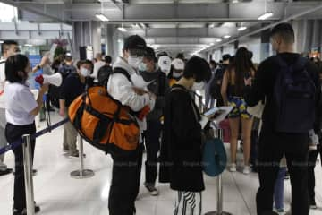 Travellers queue up for thermal scanning at Suvarnabhumi airport in Samut Prakan province before reaching immigration. (Photo: Wichan Charoenkiatpakul)