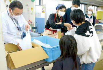 昼食のおむすびとおかずを受け取る子どもたち=10日、吉川市吉川の市社会福祉協議会