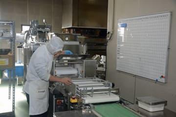 むつ市の学校給食向けパン製造工場。学校への納品状況を示すボード(右)には、ほとんど予定が入っていない=9日