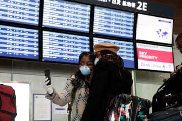 12日、フランスのシャルル・ドゴール空港で新型コロナウイルス感染対策のためマスクをする旅行者(ロイター=共同)