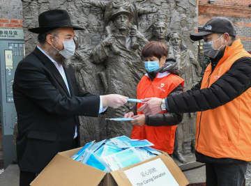 Rabbi Shalom Greenberg donates masks to a neighborhood community near the Shanghai Jewish Refugees Museum, on Feb 3. TAO LEI/FOR CHINA DAILY
