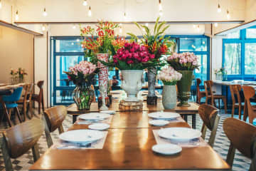 Below Natural lights and installation of fresh cut flowers lend to the cafe a gracious warmth.
