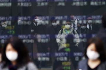 13日、東京都内の株価ボードに反射して写る、マスク姿の人たち(AP=共同)