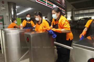 Staff busily clean Mor Chit bus terminal in Chatuchak district of Bangkok on Friday, when the Public Health Ministry announced five new local Covid-19 cases, raising the total to 75. (Photo: Nutthawat Wicheanbut)
