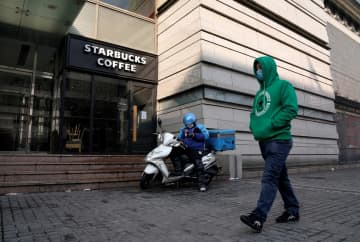 A man wearing a face mask walks past a deliveryman as he waits outside a Starbucks store in Beijing, China, Feb 7, 2020. [Photo/Agencies]
