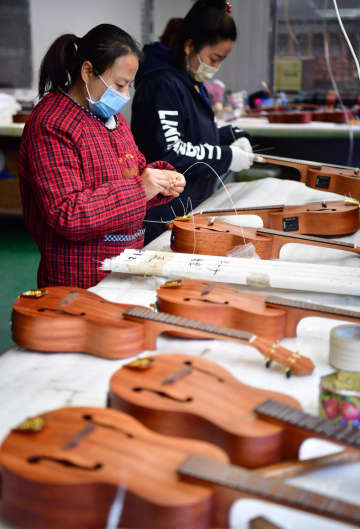 Workers assemble musical instruments ordered from overseas at a factory in Hanzhong, Shaanxi province, on Thursday. [SHAO RUI/XINHUA]
