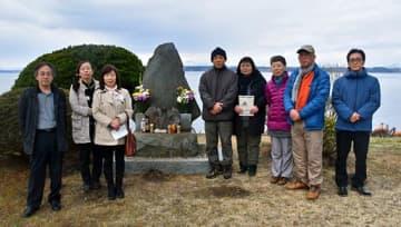 慰霊碑に花を手向け、記念写真に納まる三宅教諭の遺族や教え子、近くの住民たち