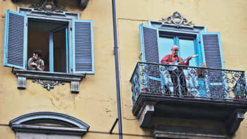 A resident looks out of his apartment window as another plays the guitar on a balcony during Italy's coronavirus crisis in Turin on Friday. MASSIMO PINCA / REUTERS