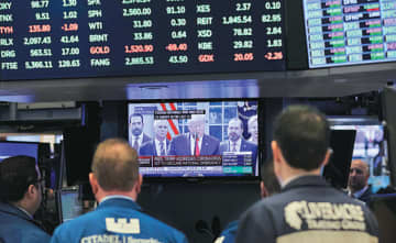 Traders listen at the New York Stock Exchange to President Donald Trump's televised speech from the White House on Friday in New York. MARK LENNIHAN / ASSOCIATED PRESS