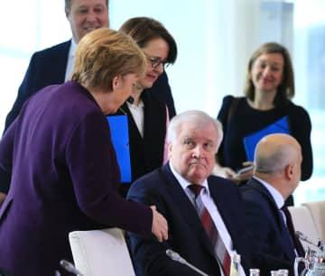 ドイツのゼーホーファー内相(中央)に握手を拒まれたメルケル首相(左)=2日、ベルリン(ゲッティ=共同)