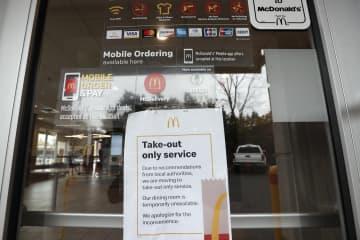 マクドナルドの店頭に貼られた告知。持ち帰りに限定するとしている=17日、米ノースカロライナ州・チャペルヒル(AP=共同)