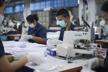 Workers assemble face masks at a factory. The government has asked garment factories to sell masks for five baht a piece.
