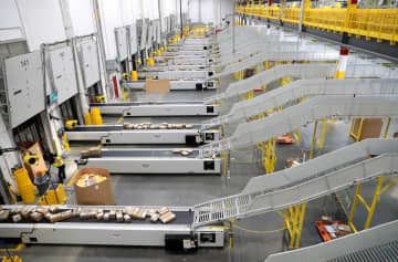 Amazon is hiring 100,000 workers and boosting hourly wages to handle the surge in demand in shipments due to the coronavirus pandemic. In a file photo, the outbound shipping dock at Amazons West Deptford fulfillment center is shown. (Tim Hawk/)