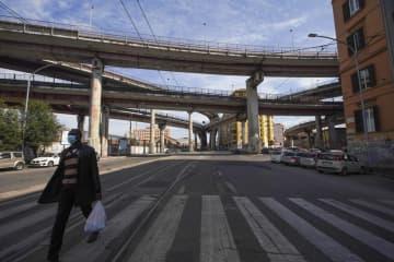 閑散としたローマの道路を歩く男性=18日(AP=共同)