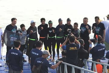 """The seven swimmers, with actor-singer Phakhin """"Tono"""" Khamwilaisak fourth from left, pose for a group photo before beginning their swim for the One Man & the Sea campaign to raise environmental awareness in Surat Thani province. (Photo by Supapong Chaolan)"""