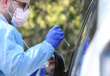 A medical technician at the at Riverside Medical Group command center administers a COVID-19 test on a patient inside an automobile at Riverside's drive-up facility in Secaucus on March 16.  (Andrew Mills   NJ Advance Media/)