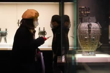 A visitor at the Bronze Exhibition Hall. At present, nine of Shanghai Museum's exhibition halls are open, including the display of bronze, ceramics, calligraphy and paintings.[Photo by Gao Erqiang/China Daily]