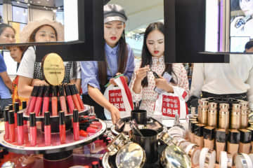 Customers check out cosmetics at a duty-free shop in Sanya, Hainan province. [Photo/China News Service]