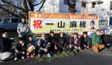 一山麻緒選手の五輪出場を祝う横断幕を掲げる鹿島自治会のメンバーら=出水市知識町