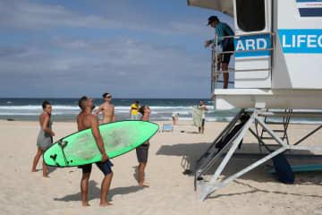 21日、海水浴客らに閉鎖を伝える監視員=シドニーのボンダイビーチ(ロイター=共同)