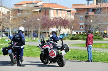 20日、イタリア中部グロッセトで市民に話し掛ける警察官(AP=共同)