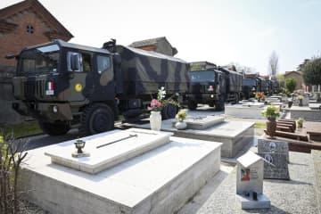イタリア北部で、新型コロナウイルスの犠牲者の遺体を乗せて墓地に到着した軍のトラックの列=21日(AP=共同)
