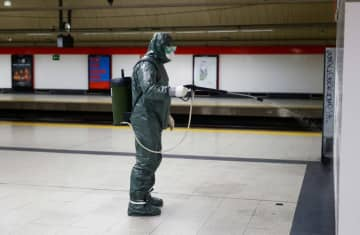 A Military Emergency Unit member disinfects a metro station due to coronavirus in Madrid, Spain. (photo credit: REUTERS/JAVIER BARBANCHO)