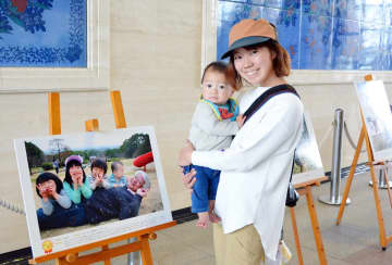 大賞に選ばれた自身の作品「みどりいっぱい!佐賀平野のように大きくなぁれ」の前で笑顔を見せる石丸晶子さんと息子の晋二郎くん=佐賀県庁