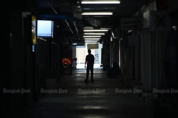 A man walks through deserted shops in Siam Square on Sunday after the Bangkok Metropolitan Administration ordered malls and many other places to close to contain the coronavirus spread. (Photo by Apichart Jinakul)
