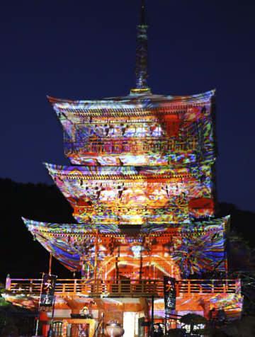 プロジェクターで色とりどりの模様が映し出される那智山青岸渡寺の三重塔=22日、和歌山県那智勝浦町
