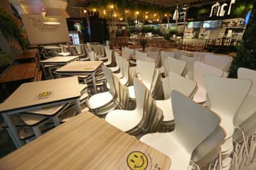 Tables and chairs at a dine-in restaurant at The Mall Bang Kapi shopping centre are stacked up after restaurants in the capital and surrounding provinces were ordered to stop taking sit-down customers.Varuth Hirunyatheb