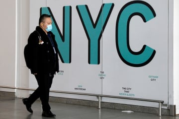 A traveler wears a face mask as a preventive measure during the outbreak of coronavirus disease (COVID-19) as he arrives at John F. Kennedy International Airport in New York City, US, March 20, 2020. [Photo/Agencies]