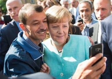ベルリンで難民と写真を撮るドイツのメルケル首相(中央)=2015年9月(AP=共同)