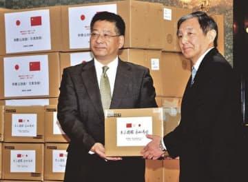 中国駐大阪総領事館の何振良総領事(左)から新型コロナウイルス感染症の対策の医療用資材の寄贈を受ける仁坂吉伸知事=和歌山県庁で